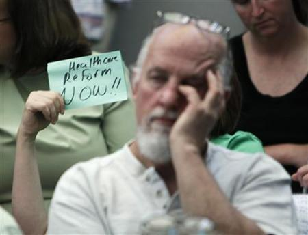A person holds up a small sign reading ''health reform now'' at a town hall meeting on healthcare reform hosted by Rep. Mike Coffman (R-CO) in Littleton, Colorado August 12, 2009. REUTERS/Rick Wilking