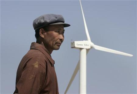 A man stands in front of a windmill at the Gansu Jieyuan Wind Power Company on the outskirts of Yumen, northwest China's Gansu province April 29, 2007. REUTERS/Jason Lee