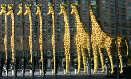 A woman looking at a life-size giraffe built of 'Lego' bricks is reflected in a window next to the so-called 'Legoland Discovery Centre' in Berlin March 28, 2007. REUTERS/Tobias Schwarz