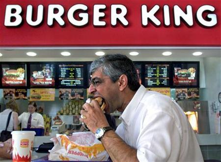 A man bites into his Whopper burger as he eats lunch at the newly-opened Burger King in the town August 9. REUTERS/David Silverman