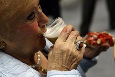 <p>Una donna beve un bicchiere di birra in una fiera a Madrid. REUTERS/Juan Medina</p>