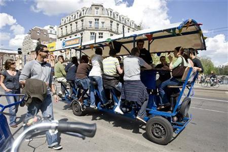 Tourists cycle as they drink beer and sing karaoke on a beer bike in Amsterdam June 12, 2009. The beer bike is a mobile, pedal-powered bar. REUTERS/Robin van Lonkhuijsen/United Photos