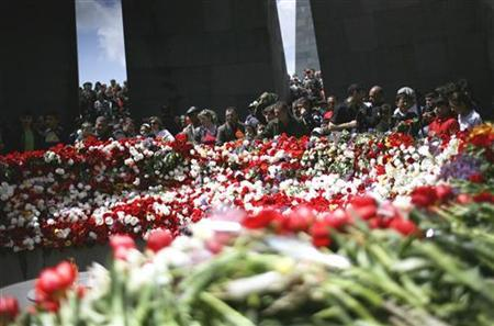 People gather near flowers at a ceremony marking the anniversary of mass killings of Armenians in 1915, in Yerevan April 24, 2009. REUTERS/Matt Robinson