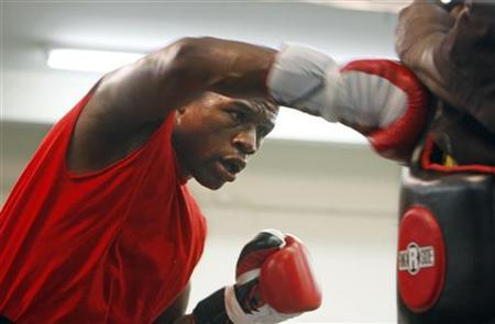 Boxer Floyd Mayweather Jr. of the U.S. hits a body pad worn by assistant trainer Nate Jones during a workout in his gym in Las Vegas, Nevada, June 11, 2009. REUTERS/Las Vegas Sun/Steve Marcus