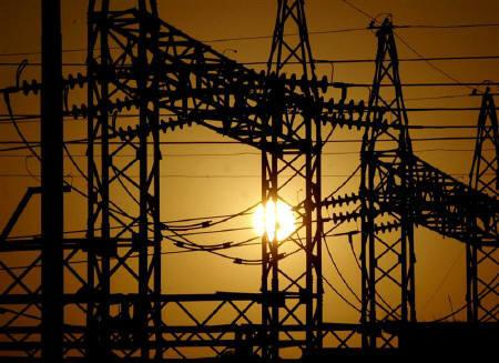 The sun sets behind electric pylons in Allahabad in this February 2006 file photo. REUTERS/Jitendra Prakash