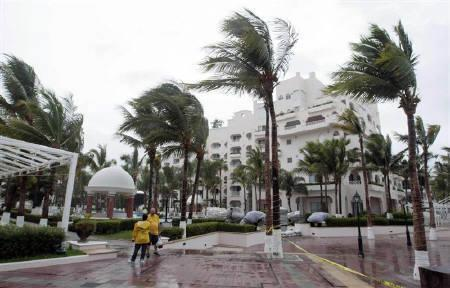 Palm trees are blown by strong winds in front of a hotel in Cabo San Lucas in Mexico's state of Baja California, as Hurricane Jimena approaches, September 1, 2009. REUTERS/Henry Romero