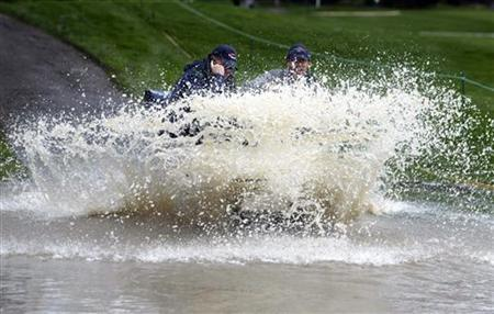 Two workers drive their golf cart through rushing water on the ninth fairway cart path after heavy rain caused flooding one day prior to the start of Accenture Match Play World Golf Championships at the La Costa Country Club in Carlsbad, California, February 25, 2003. REUTERS/Mike Blake