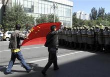 <p>Представители китайской народности хань держат флаг Китая во время протеста на улицах города Урумчи 3 сентября 2009 года. Китайские силы безопасности разогнали в пятницу многотысячный митинг протеста в столице Синьцзян-Уйгурского автономного района. Участники, представители народности хань, уже второй день подряд требуют улучшить ситуацию с безопасностью в городе и наказать уйгуров, виновных в организации массовых беспорядков в июле. REUTERS/Stringer</p>