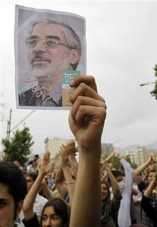 A supporter of Iran's moderate presidential candidate Mirhossein Mousavi holds up a poster of Mousavi during a protest against the election results in Tehran in this June 13, 2009 file photo. REUTERS/Ahmed Jadallah/Files