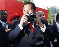 <p>Venezuela's President Hugo Chavez pose while holding a camera for photographers during a red carpet at the 66th Venice Film Festival September 7, 2009. REUTERS/Tony Gentile</p>
