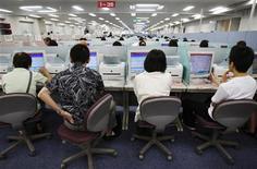 <p>Redattori di un'agenzia stampa davanti ai pc. REUTERS/Yuriko Nakao</p>