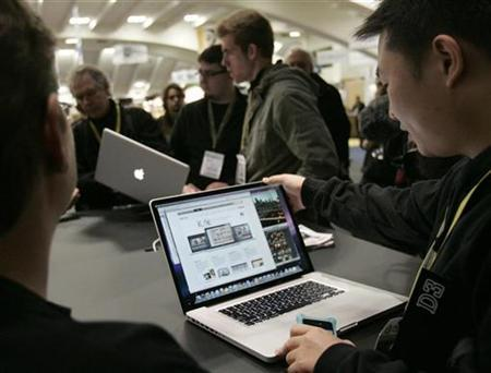 Attendees to the Macworld Convention and Expo 2009 look over the new 17-inch MacBook in San Francisco, California January 6, 2009. REUTERS/Robert Galbraith