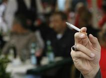 <p>A smoker holds a cigarette in a public place near the Stade de Geneve in Geneva August 22, 2007. REUTERS/Denis Balibouse</p>