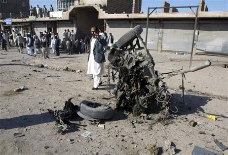An Afghan man takes a picture with his mobile phone at the scene of a roadside bomb blast in Herat province September 27, 2009. REUTERS/Mohammad Shioab