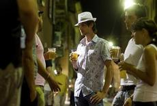 <p>Young Italians drink beer in downtown Milan August 20, 2009. REUTERS/Paolo Bona</p>