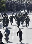 <p>Представители народности хань убегают от сотрудников служб безопасности КНР в Урумчи 4 сентября 2009 года. Китай объявил о первых обвинениях, предъявленных в связи с июльскими беспорядками в Синьцзянь- Уйгурском районе. REUTERS/Nir Elias</p>