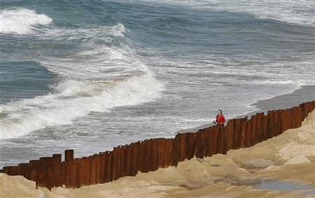 A woman walks next to a wall construction site at south Coogee beach in Sydney August 12, 2009. REUTERS/Daniel Munoz