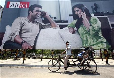 A rickshaw driver talks on his mobile phone as he rides past a billboard outside a railway station in the northern Indian city of Chandigarh May 26, 2009. REUTERS/Ajay Verma