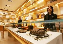 <p>Sales people wait at Louis Vuitton Maison during the media preview as it opens at the Landmark in Central, a business district in Hong Kong December 8, 2005. REUTERS/Paul Yeung</p>
