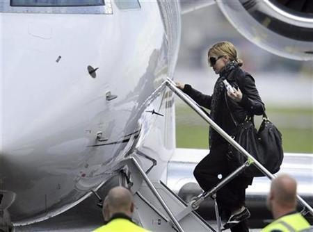 Pop star Madonna boards the plane as she leaves Helsinki, August 7, 2009. REUTERS/LEHTIKUVA/Roni Rekomaa