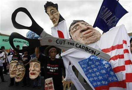 An activist pretends to cut off the head of an effigy of U.S. President Barack Obama during a demonstration outside the United Nations Building in Bangkok, where talks on climate change are being held, October 5, 2009. REUTERS/Chaiwat Subprasom