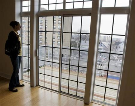 Prospective home buyer Jessica Doctoroff looks out the windows of a condominium for sale in Somerville, Massachusetts April 2, 2009. REUTERS/Brian Snyder