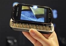<p>Una mujer sostiene el móvil de Armani durante su lanzamiento en Milán, 9 oct 2009. La casa italiana de moda Giorgio Armani presentó el viernes un nuevo teléfono de 700 euros (1.032 dólares), un dispositivo elegante que pretende armonizar con los trajes del diseñador. El fundador de la empresa, Giorgio Armani, considerado el padrino de la moda italiana, hizo una breve aparición pública en el lanzamiento del teléfono inteligente Armani-Samsung, que incluye además el nuevo software de Microsoft para móviles. REUTERS/Paolo Bona</p>