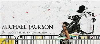 """<p>Mulher passa por banner memorial a Michael Jackson em Los Angeles. O novo single de Michael Jackson """"This Is It"""" foi lançado nesta segunda-feira nas rádios e na Internet, cerca de quatro meses depois da morte do """"rei do pop"""" devido a uma overdose de medicamentos, aos 50 anos.25/09/2009.REUTERS/Danny Moloshok</p>"""