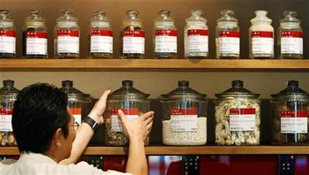 A shop assistant arranges jars containing roots and herbs at a Chinese medicine shop in Singapore, February 17, 2009. REUTERS/Vivek Prakash
