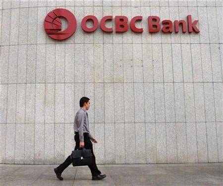 A man walks past OCBC bank in Singapore's central business district, August 6 2002. REUTERS/Jonathan Searle JS