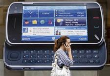 <p>Una donna parla al telefonino mentre passa accanto ad un manifesto pubblicitario della Nokia. REUTERS/Luke MacGregor</p>