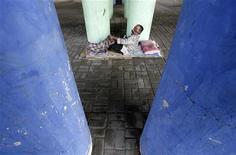 <p>Vite ai margini. Un homeless si sistema per terra in una via di Jakarta. REUTERS/Supri</p>