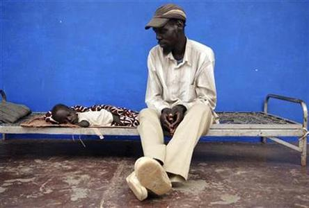 A man sits next to his sick son at the Abyei hospital, which was looted, in Abyei town in central Sudan, July 8, 2009. REUTERS/Andrew Heavens
