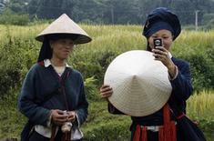 <p>Strumento globale. Una contadina vietnamita scatta una fotografia con il suo cellulare. REUTERS/Kham</p>