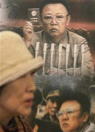 A Japanese tourist walks past a display showing pictures of North Korean leader Kim Jong-il at a South Korean observation post near the demilitarized zone separating the two Koreas, north of Seoul, October 13, 2009. REUTERS/Lee Jae-Won