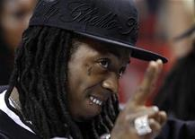 <p>Rap recording artist Lil Wayne watches the Miami Heat play the Atlanta Hawks in Game 4 of their NBA Eastern Conference playoff series in Miami, Florida April 27, 2009. REUTERS/Hans Deryk</p>