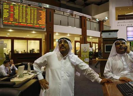 Traders look at trading boards at the Dubai Stock Exchange October 7, 2008. REUTERS/Ahmed Jadallah