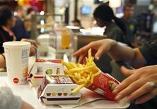 <p>Работник McDonald's отдает клиенту заказ в закусочной в Страсбурге 17 сентября 2008 года. Мировой финансовый кризис не только нанес жестокий удар по экономике Исландии, но и лишил жителей и туристов в маленьком островном государстве возможности быстро перекусить в забегаловках под брендом McDonald's Corp. REUTERS/Vincent Kessler</p>
