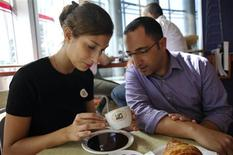 <p>Israeli waitress Lin Tabachnik (L) reads the coffee grounds of customer Asaf Mor at a coffee shop in Tel Aviv, October 27, 2009. REUTERS/Amir Cohen</p>