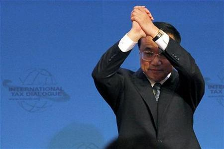 China's Vice Premier Li Keqiang (R) reacts to the audience during the opening ceremony of the 3rd International Tax Dialogue Global Conference in Beijing October 26, 2009. REUTERS/David Gray