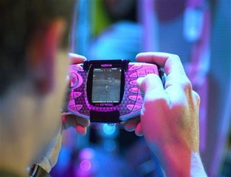 An attendee at the Electronic Entertainment Expo plays a prototype of the Nokia mobile game deck N-Gage in Los Angeles, May 15, 2003. REUTERS/Brad Rickerby