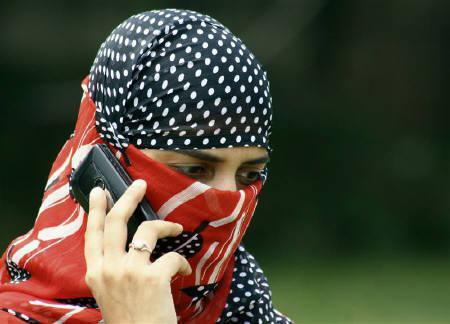 A girl speaks on a mobile phone in Jammu in this August 24, 2007 file photo. The government on Friday banned pre-paid mobile phone connections in Jammu and Kashmir over security concerns. REUTERS/Amit Gupta/Files