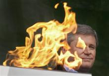 <p>Canadian Prime Minister Stephen Harper watches ceremonies from behind the Olympic Flame following its arrival in Victoria, British Columbia October 30, 2009. REUTERS/Andy Clark</p>