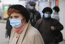 <p>Alcune persone per strada con la mascherina chirurgica per proteggersi dal virus H1N1. REUTERS/Viktor Gurniak</p>
