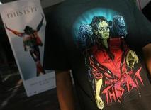 """<p>Поклонник Майкла Джексона стоит на фоне афишы документального фильма """"This Is It"""" (""""Вот и все"""") в кинотеатре Бомбея 28 октября 2009 года. Нашумевший фильм о Майкле Джексоне """"Вот и все"""" возглавил мировой кинопрокат, однако результаты, полученные в Северной Америке, вряд ли впечатлили создателей ленты.REUTERS/Arko Datta</p>"""