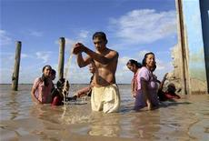<p>Surinamese Hindus take a ritual bath in the Suriname river on the first day of the Navratri festival of worship and dance in Paramaribo March 27, 2009. REUTERS/Ranu Abhelakh</p>