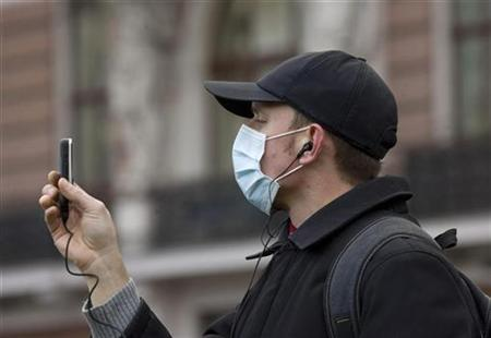 A man wearing face mask takes a photo using a mobile phone in centre of Lviv, November 1, 2009. REUTERS/Vasily Fedosenko