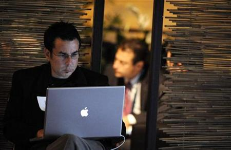 An attendee works on a computer at the 2009 Milken Institute Global Conference in Beverly Hills, California in this April 28, 2009 file photo. REUTERS/Phil McCarten