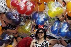<p>Una visitante sostiene globos mientras posa para una fotografía en Disneylandia de Hong Kong, 4 nov 2009. El acuerdo de la compañía Walt Disney para construir uno de sus parques temáticos característicos en Shanghái marca un gran avance para medios de comunicación y firmas de entretenimiento occidentales que intentan ingresar al difícil mercado chino. La aprobación del Gobierno para el parque temático el miércoles pone fin a años de negociaciones entre Disney y las autoridades chinas, las cuales son cautas ante una gran influencia extranjera en los delicados sectores de medios y cultura popular. REUTERS/Tyrone Siu</p>
