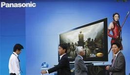<p>Personas caminan cerca de un afiche publicitario de Panasonic en Tokio, 4 nov 2009. La japonesa fabricante de electrónica de consumo Panasonic Corp anunció que prevé lanzar el jueves una oferta pública de acciones de Sanyo Electric Co, con lo que se acercaría a convertirse en una potencia en baterías de autos híbridos y otros negocios de energía ecológica. REUTERS/Kim Kyung-Hoon</p>